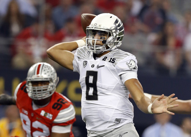 Jan 12, 2015; Arlington, TX, USA; Oregon Ducks quarterback Marcus Mariota (8) throws a touchdown pass to wide receiver Keanon Lowe (not pictured) in the first quarter against the Ohio State Buckey ...