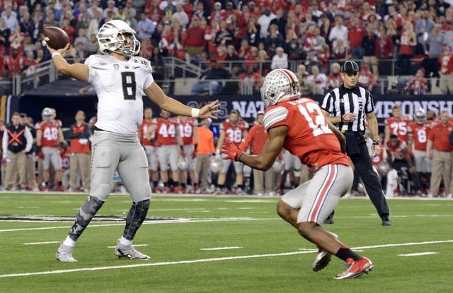Jan 12, 2015; Arlington, TX, USA; Oregon Ducks quarterback Marcus Mariota (8) throws a pass against Ohio State Buckeyes cornerback Doran Grant (12)during the third quarter in the 2015 CFP National ...