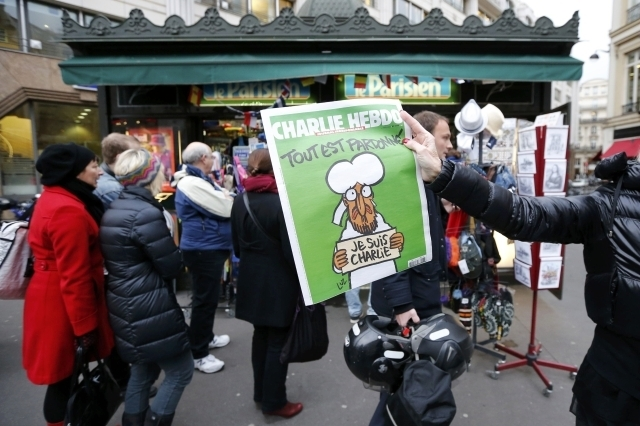 """A woman shows a copy of the new issue of satirical French weekly Charlie Hebdo entitled """"Tout est pardonne"""" (""""All is forgiven""""), which shows a caricature of Prophet Muhammad, in front of a kiosk i ..."""