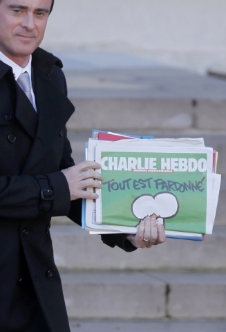 """French Prime Minister Manuel Valls holds a copy of Charlie Hebdo with the title """"Tout est pardonne"""" (""""All is forgiven"""") as he leaves the weekly cabinet meeting at the Elysee Palace in Paris, Wedne ..."""
