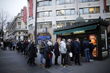 """People queue to get a copy of satirical French magazine Charlie Hebdo new issue titled """"Tout est pardonne"""" (""""All is forgiven"""") showing a caricature of Prophet Muhammad in front of a kiosk in Paris ..."""