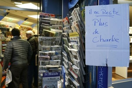 """A handwritten sign, which reads """"No more Charlie,"""" is displayed after it sold out the limited stock of the satirical newspaper in Paris, Wednesday, Jan. 14, 2015. (Reuters/John Schults)"""