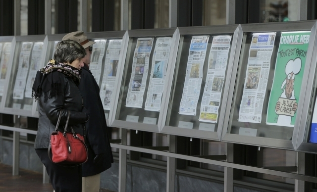 A couple looks at the latest edition of Charlie Hebdo seen with U.S. newspapers that are displayed daily at the Newseum in Washington, D.C., Wednesday, Jan. 14, 2015. The first edition of Charlie  ...