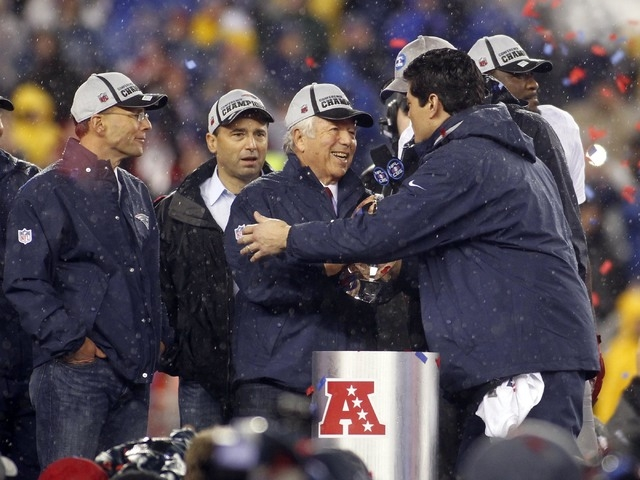 New England Patriots former player Tedy Brudschi present New England Patriots owner Robert Kraft with the Lamar Hunt Trophy after beating the Indianapolis Colts in the AFC Championship Game at Gil ...