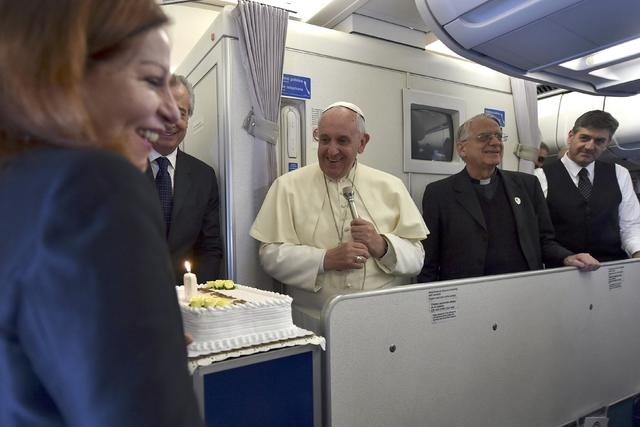 Journalist Maria Valentina Alzraki Crastich receives a birthday cake from Pope Francis during the flight  back from Manila to Rome, January 19, 2015. (REUTERS/Giuseppe Cacace/Pool)