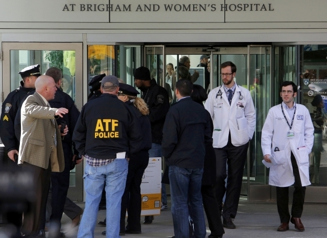 Local, state and federal law enforcement officials gather outside the building where a shooting occurred at Brigham and Women's hospital in Boston, Tuesday, Jan. 20, 2015. One person has been shot ...