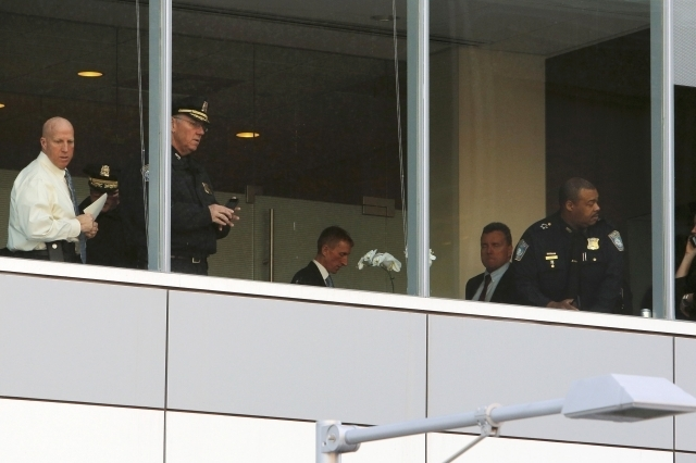 Boston Police officers, including Commissioner William Evans, center, work inside the building where a shooting occurred at Brigham and Women's hospital in Boston, Tuesday, Jan. 20, 2015. One pers ...