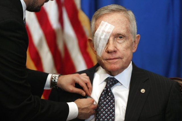 An aide attaches a microphone as U.S. Senate Minority Leader Harry Reid, D-Nev., sits down for a news conference in his office at the U.S. Capitol in Washington, Thursday, January 22, 2015. Reid i ...