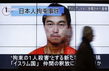 A man walks past screens displaying a television news program showing an image of Kenji Goto, one of two Japanese citizens taken captive by Islamic State militants, on a street in Tokyo, Sunday, J ...