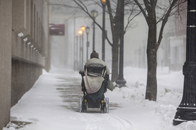 A man makes his way through New Haven, Connecticut, Tuesday, Jan. 27, 2015. A blizzard swept across the northeastern United States on Tuesday, dropping more than a foot of snow across Massachusett ...