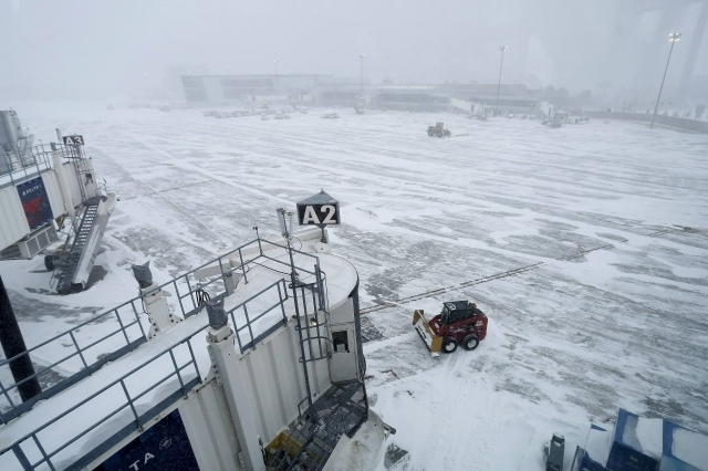 Workers use snow removal equipment to clear the tarmac at Logan Airport during a blizzard in Boston, Massachusetts, Tuesday, Jan. 27, 2015. A blizzard swept across the northeastern United States o ...