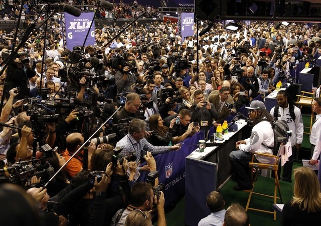 Jan 27, 2015; Phoenix, AZ, USA; Seattle Seahawks running back Marshawn Lynch sits at his podium during media day for Super Bowl XLIX at US Airways Center. (Matthew Emmons-USA TODAY Sports)