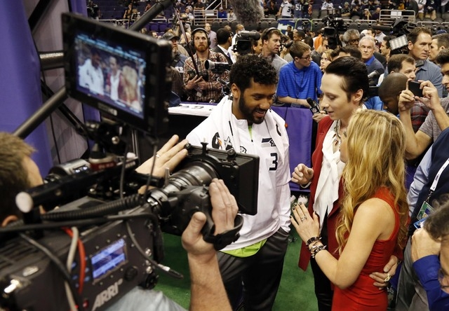 Seattle Seahawks quarterback Russell Wilson (3) is interviewed by NBC correspondents Tara Lipinski (right) and Johnny Weir during media day for Super Bowl XLIX at US Airways Center in Phoenix on J ...