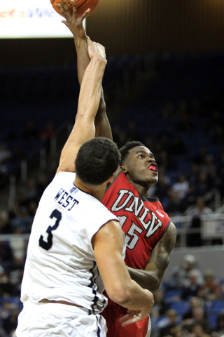 Jan 27, 2015; Reno, NV, USA; UNLV Runnin' Rebel forward Dwayne Morgan(15) shoots in front of Nevada Wolf Pack forward AJ West (3) in the second half of their NCAA basketball game at Lawlor Events  ...