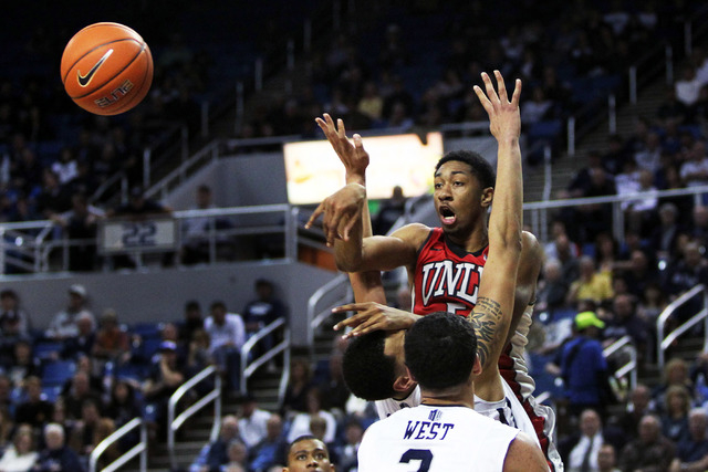 Jan 27, 2015; Reno, NV, USA; UNLV Runnin' Rebel forward Christian Wood (5) passes off in front of Nevada Wolf Pack forward Kaileb Rodriguez (50) and AJ West (3) in the second half of their NCAA ba ...
