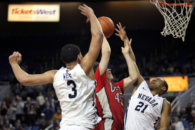 Jan 27, 2015; Reno, NV, USA; UNLV Runnin' Rebel guard Cody Doolin (45) scores between Nevada Wolf Pack forward AJ West (3) and Eric Cooper (21) in the second half of their NCAA basketball game at  ...