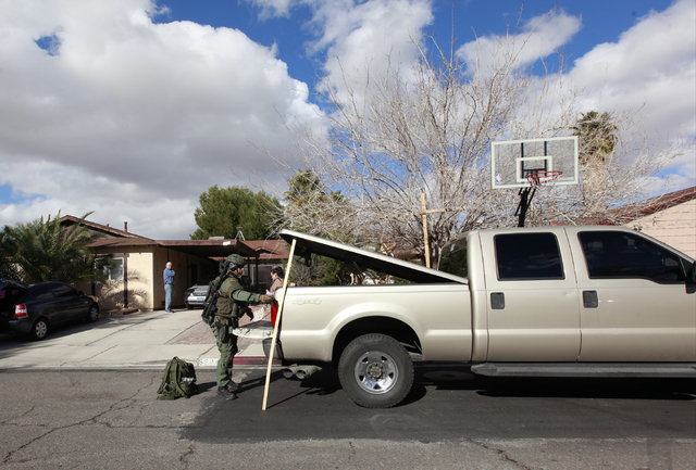 A Las Vegas SWAT officer arrives at a barricade situation on the 5600 block of Blue Sea Street near the intersection of Charleston and Nellis boulevards, in Las Vegas on Tuesday, Jan. 27, 2015. A  ...