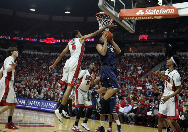 UNLV forward Christian Wood blocks a shot by UNR forward Robyn Missa in the first half of their basketball game Wednesday, Jan. 7, 2015, at the Thomas & Mack Center in Las Vegas. Looking on are UN ...