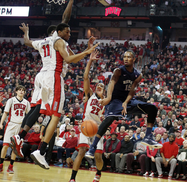 UNR guard D.J. Fenner passes around UNLV forward Christian Wood in the first half of their basketball game Wednesday, Jan. 7, 2015, at the Thomas & Mack Center in Las Vegas. Also defending are, UN ...