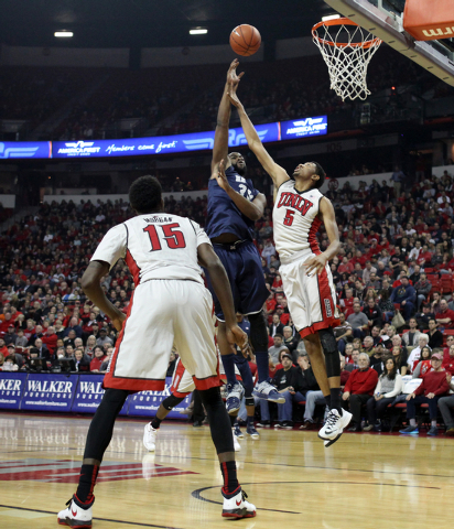 UNR center Ronnie Stevens Jr. shoots over UNLV forward Christian Wood as UNLV forward Dwayne Morgan looks on in the first half of their basketball game Wednesday, Jan. 7, 2015, at the Thomas & Mac ...