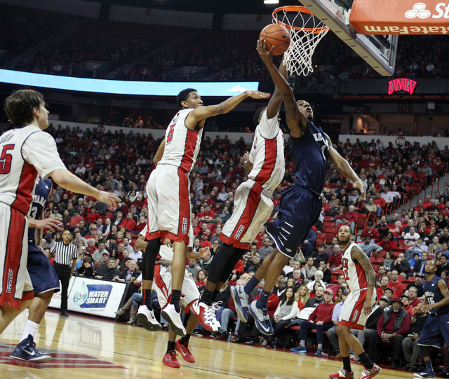 UNR guard Marqueze Coleman shoots in front of UNLV forward Christian Wood (5) and UNLV forward Goodluck Okonoboh in the first half of their basketball game Wednesday, Jan. 7, 2015, at the Thomas & ...