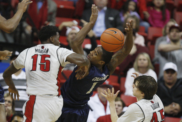 UNLV forward Dwayne Morgan swats the ball away from UNR guard Marqueze Coleman during their Mountain West Conference basketball game Wednesday, Jan. 7, 2015, at the Thomas & Mack Center. UNR won t ...