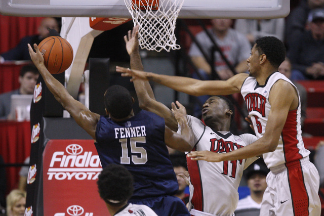 UNR guard D.J. Fenner gets a rebound away from UNLV forward Goodluck Okonoboh, center, and UNLV forward Christian Wood during their Mountain West Conference basketball game Wednesday, Jan. 7, 2015 ...