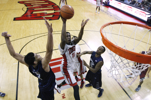 UNLV forward Goodluck Okonoboh drives between UNR forward A.J. West, left, and UNR guard D.J. Fenner during their Mountain West Conference basketball game Wednesday, Jan. 7, 2015, at the Thomas &  ...