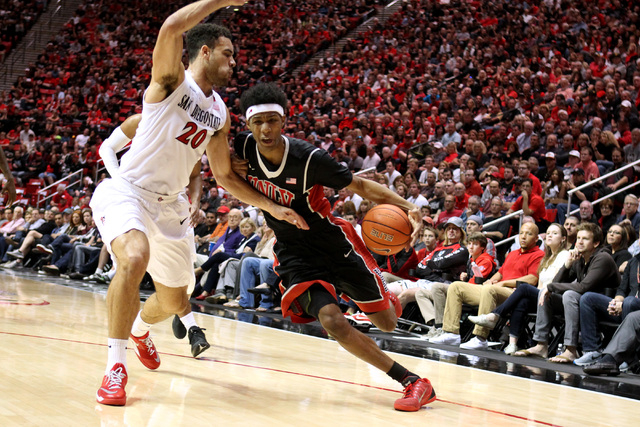UNLV guard Patrick McCaw drives around San Diego State forward J.J. O'Brien during the first half of their Mountain West Conference game Saturday, Jan. 17, 2015, at Viejas Arena in San Diego. (Sam ...