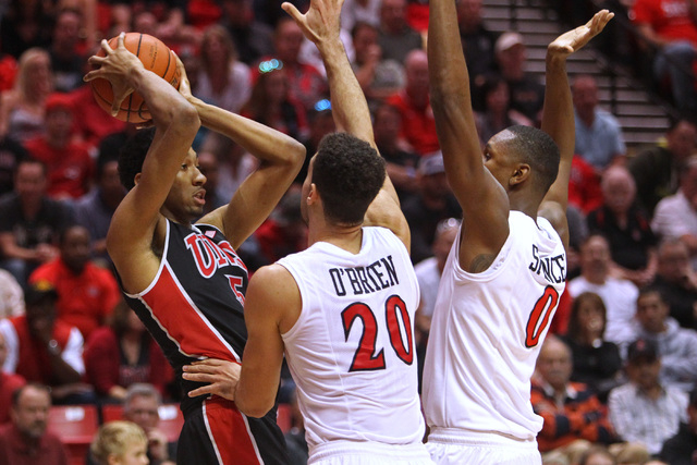 UNLV forward Chris Wood is double teamed by San Diego State forward J.J. O'Brien and forward Skylar Spencer during the second half of their Mountain West Conference game Saturday, Jan. 17, 2015, a ...
