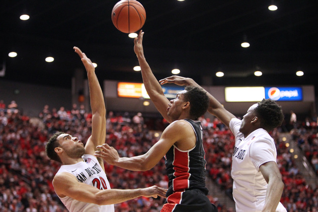San Diego State forward J.J. O'Brien, left, and guard Dakarai Allen defend a shot by UNLV guard Rashad Vaughn during the second half of their Mountain West Conference game Saturday, Jan. 17, 2015, ...