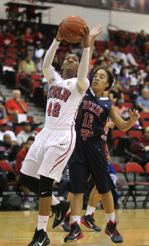 UNLV women's basketball senior guard Danielle Miller (42) shoots over Dixie State guard Leslie Tademy in the first half of an exhibition game at the Cox Pavilion Monday, Nov. 10, 2014. (K.M. Canno ...