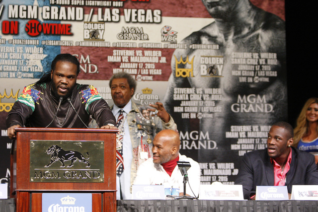 Bermane Stiverne, left, speaks during a press conference at the MGM Grand casino-hotel for his boxing bout for his World Boxing Council heavyweight championship title against Deontay Wilder Thursd ...