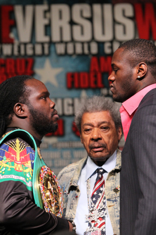 """Boxing promoter Donald """"Don"""" King, center, watches Bermane Stiverne, left, and Deontay Wilder, face off during a press conference at the MGM Grand casino-hotel for their upcoming boxing  ..."""