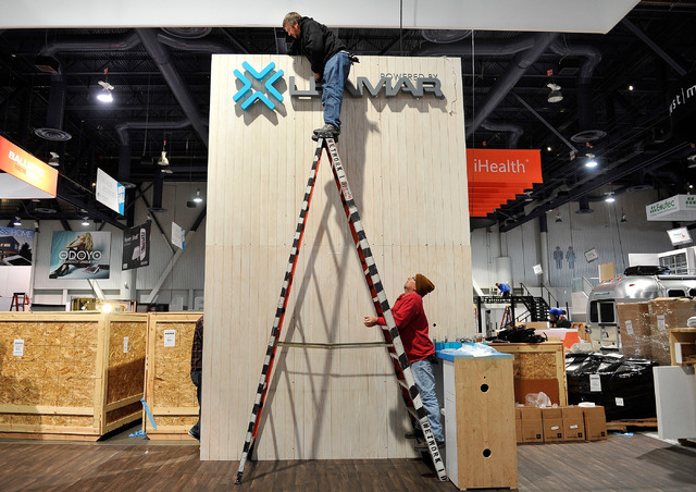 Rodney Putnam, left, and Perry Godzisz work to assemble a booth for CES at the Las Vegas Convention Center on Friday, Jan. 2, 2015, in Las Vegas. (David Becker/Las Vegas Review-Journal)