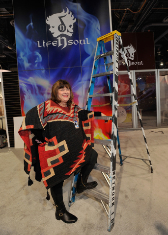 Chris Harvey, owner of Design Factory, poses with a ladder in one of the booths her crew assembled for CES at the Las Vegas Convention Center on Friday, Jan. 2, 2015, in Las Vegas. (David Becker/L ...