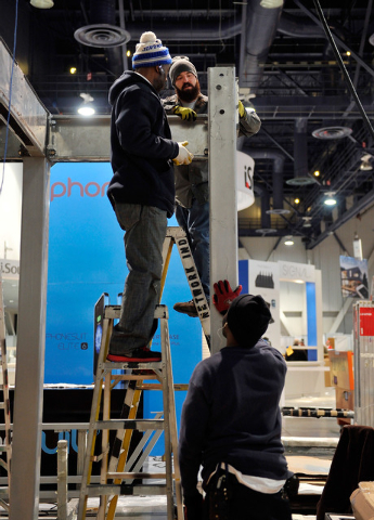 Workers from left, Brent Carler, Thomas Howe and James Benson assemble a support structure for a booth at CES at the Las Vegas Convention Center on Friday, Jan. 2, 2015, in Las Vegas. (David Becke ...