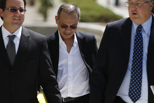 Paul Phua, center, walks to Lloyd George Federal Courthouse in Las Vegas with his attorneys Richard Schonfeld, left, and David Chesnoff, for his arraignment Tuesday, Aug. 5, 2014. (Erik Verduzco/L ...
