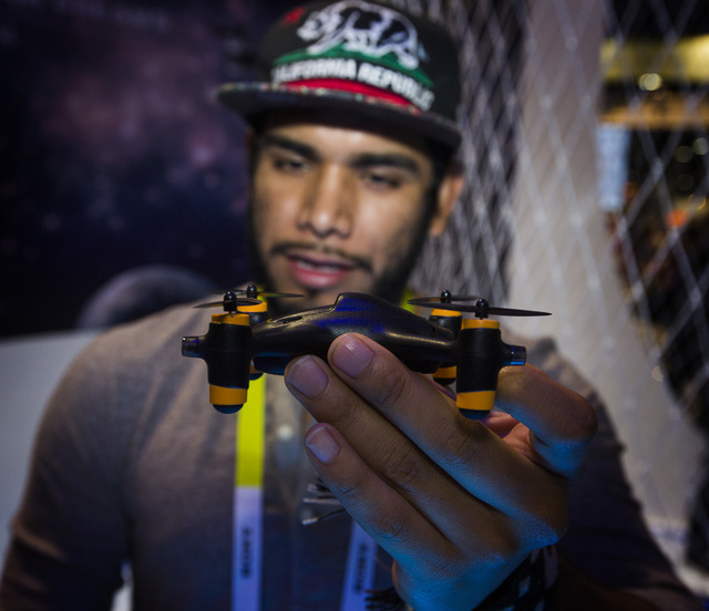 Wilson Rodriguez looks at a Hubsan FPV x4 mini quadcopter Tuesday, Jan. 6, 2015 during Consumer Electronic Show in the Las Vegas Convention Center. The drone is equipped with a video camera. Aroun ...