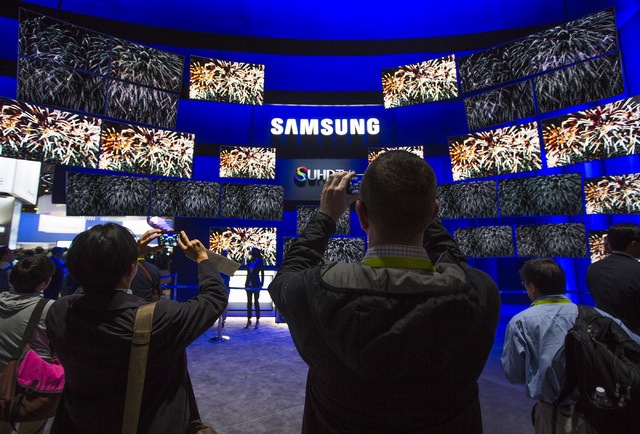 People stand at the entrance of the Samsung booth Tuesday, Jan. 6, 2015 during Consumer Electronic Show in the Las Vegas Convention Center. Around 160,000 people with 25% coming from overseas are  ...
