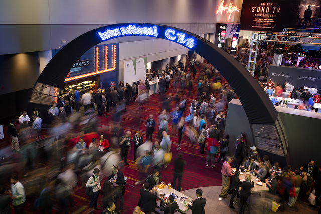 People walk in the Las Vegas Convention Center Tuesday, Jan. 6, 2015 during Consumer Electronic Show. Around 160,000 people with 25% coming from overseas are attending the  four-day CES. (Jeff Sch ...