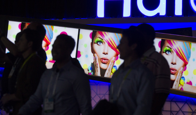 People walk by the Haier America  booth Tuesday, Jan. 6, 2015 during Consumer Electronic Show in the Las Vegas Convention Center. Around 160,000 people with 25% coming from overseas are attending  ...