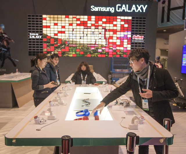 People place accessories at the Samsung Galaxy booth in the Las Vegas Convention Center  on Monday, Jan. 5, 2015. An estimate of 160,000 people will be attending the 2015 International Consumer El ...