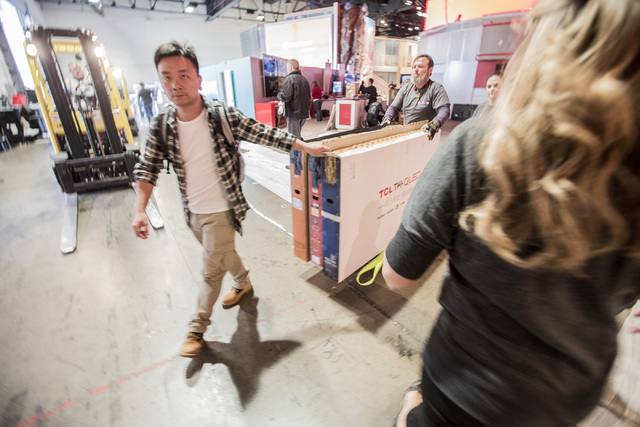 Workers move big screen TVs at the Las Vegas Convention Center on Monday, Jan. 5, 2015. An estimate of 160,000 people will be attending the 2015 International Consumer Electronics Show ,which begi ...