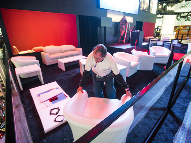 Anthony Bucci cleans at the Monster booth in the Las Vegas Convention Center on Monday, Jan. 5, 2015. An estimate of 160,000 people will be attending the 2015 International Consumer Electronics Sh ...