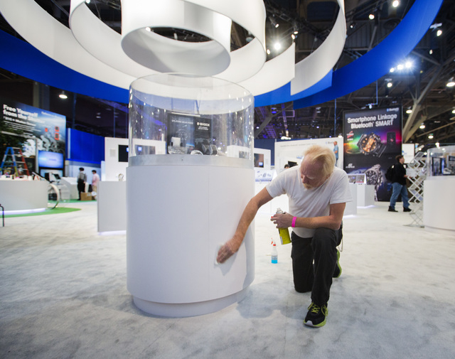 Charles Bailey cleans at display at the Casio booth in the Las Vegas Convention Center  on Monday, Jan. 5, 2015. An estimate of 160,000 people will be attending the 2015 International Consumer Ele ...