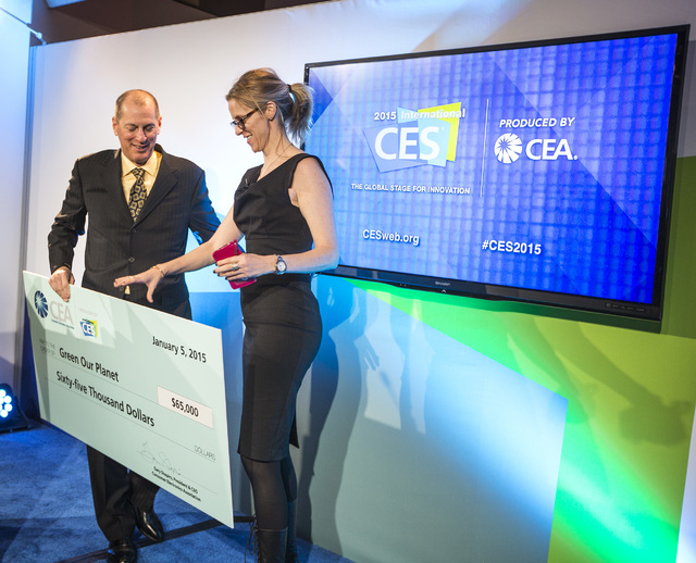 Gary Shapiro, left, president and CEO of Consumer Electronics Association, presents Ciara Byrne, co-founder of Green Our Planet, with a $65,000 check, Monday, Jan. 5, 2015, at the Las Vegas Conven ...