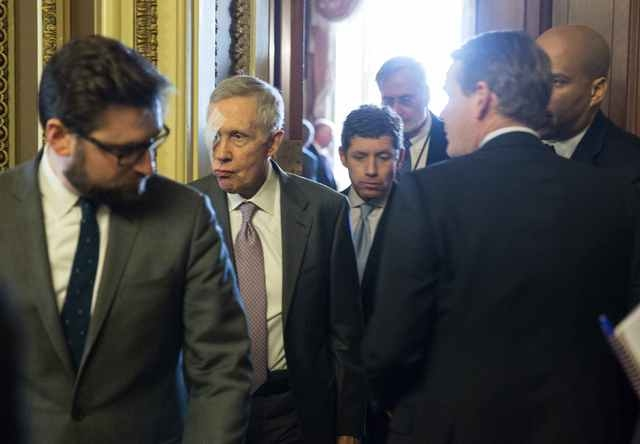 Senate Minority Leader Harry Reid (D-NV) walks from the Democratic caucus luncheon on Capitol Hill in Washington January 20, 2015. Reid injured his head and eye after an accident while exercising. ...