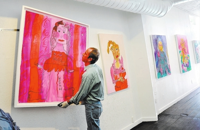 Pete Walsh rehangs a piece of art at the gallery. (David Becker/View)