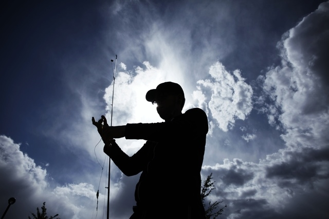 A fisherman, who declined to give his name, fixes his hook while fishing at Lorenzi Park in Las Vegas Wednesday, May 7, 2014. (John Locher/Las Vegas Review-Journal)